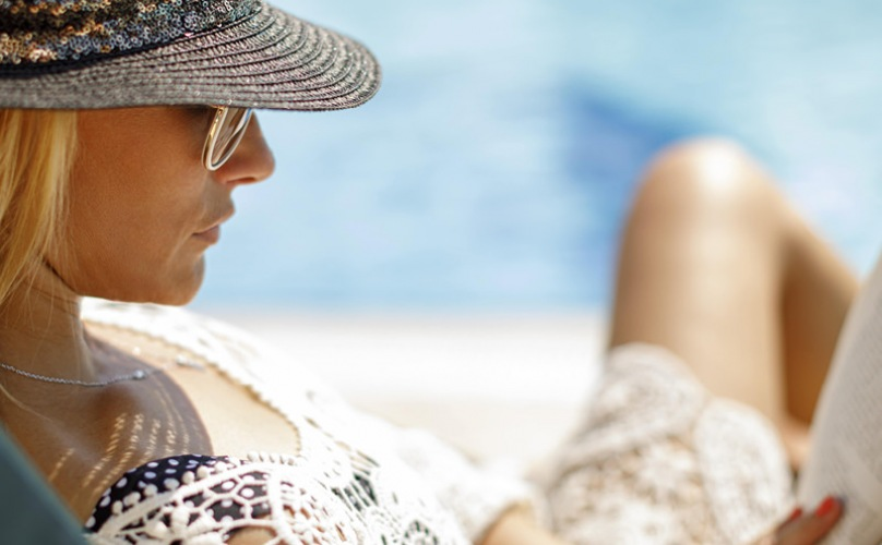 Lady sitting by the pool with large sun hat on reading a book.