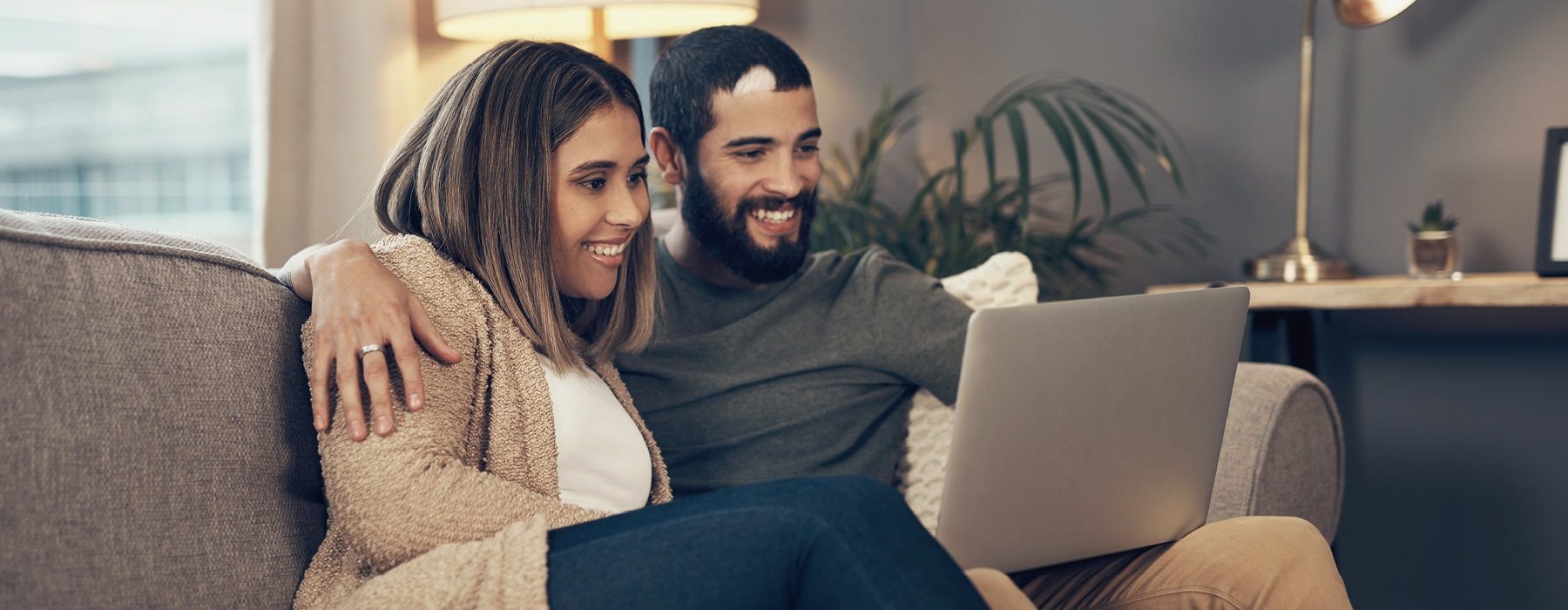 Man and woman on laptop sitting on couch.