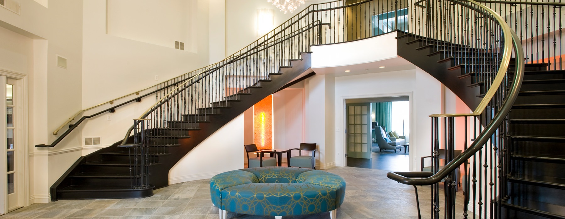 Large lobby with dual curving staircase and circular couch seating.